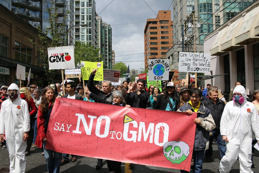"People march, carrying signs like ""Say no to GMO."" Some wear hazmat suits."