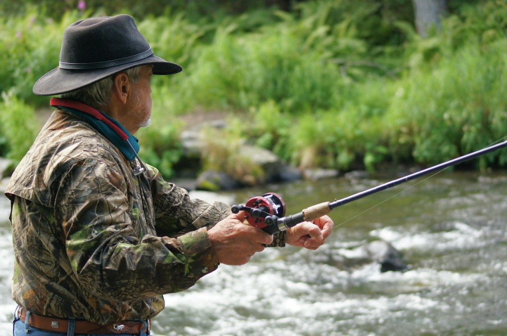 A man wearing a camouflage jacket holds a fishing rod beside a river.