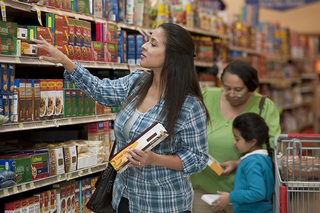 A woman in a grocery store looks at the shelves, holding a box of pasta.