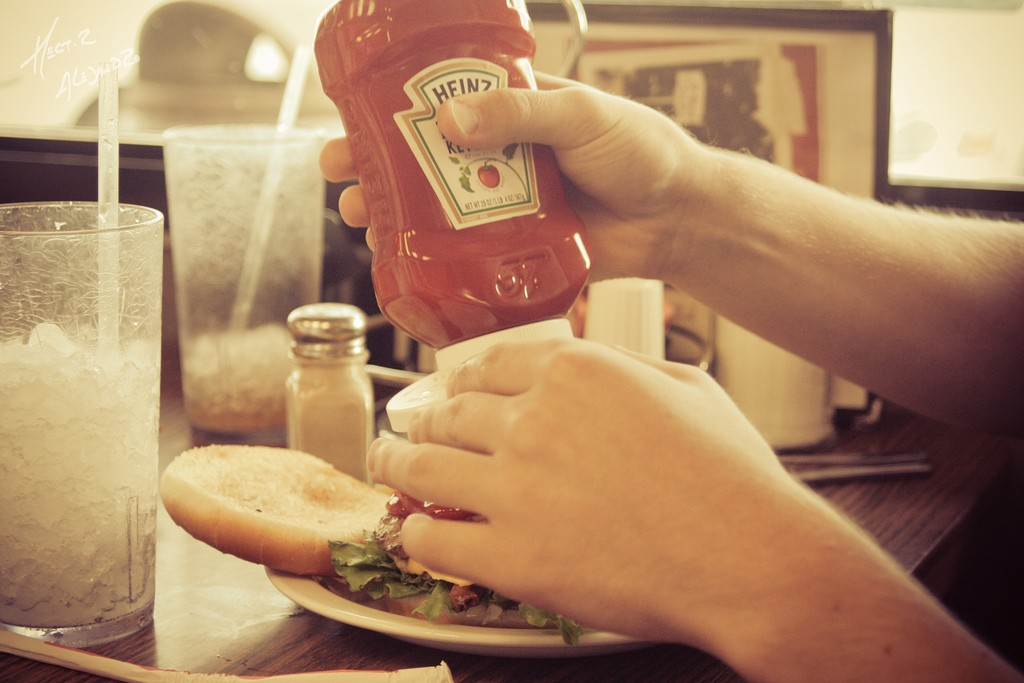 A person squeezes ketchup onto a hamburger.