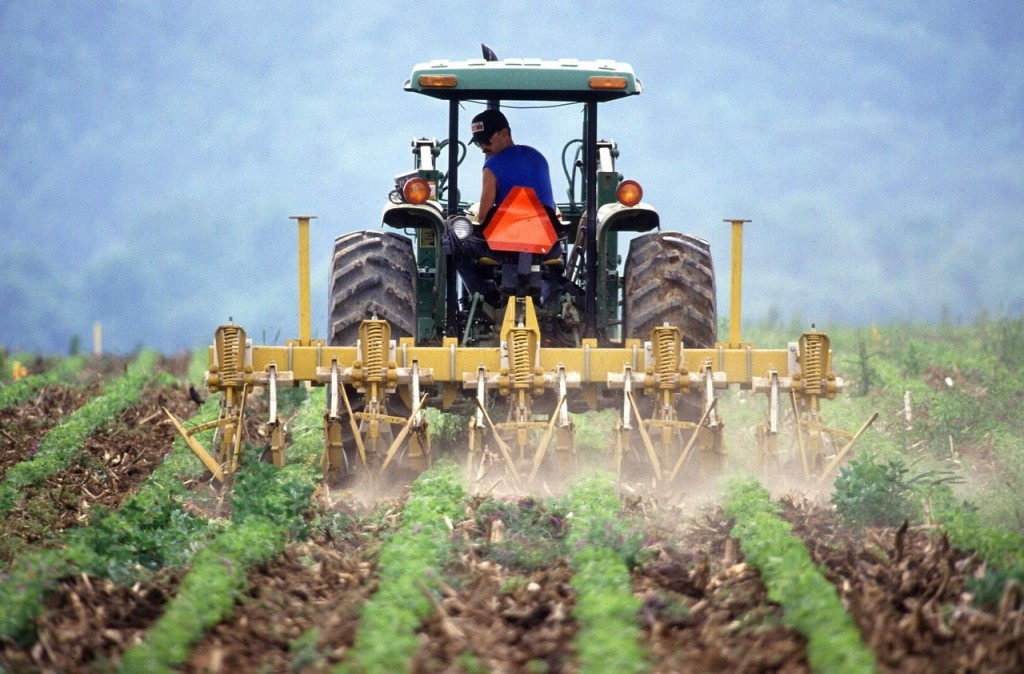 A man plows a field with a tractor.