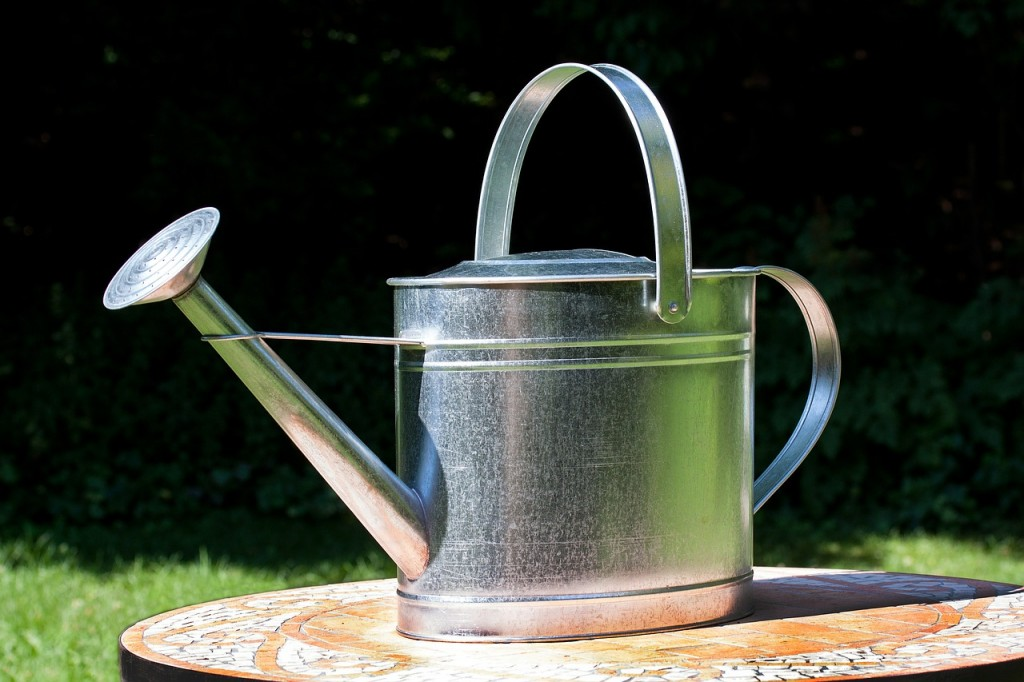 A metal watering can sitting on a patio table.