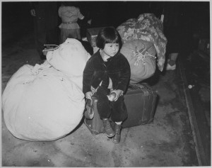 A_young_evacuee_of_Japanese_ancestry_waits_with_the_family_baggage_before_leaving_by_bus_for_an_assembly_center
