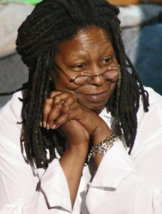 A woman with dreadlocks and a warm smile clasps her hands beside her face.