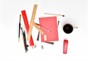 Rulers, paintbrushes, pencils, notebooks, a stapler, other office supplies and a cup of coffee.