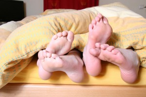 Two pairs of feet at the foot of a bed, peeking out from under a yellow blanket.