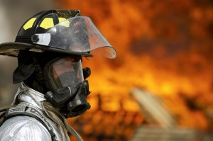 A firefighter stands in front of a distant fire.