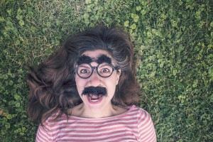 A woman lies on grass, wearing a fake moustache, big nose, glasses, and bushy eyebrows.