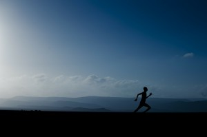 A runner is silhouetted against a landscape of mountains and blue sky with clouds.