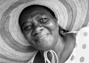 A smiling woman wears a polka-dotted blouse sun hat tied beneath her chin.