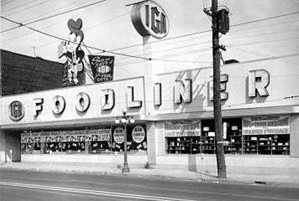 """An IGA grocery store says """"Foodliner"""" in big letters outside. A cartoon character looms above it."""