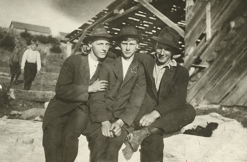 Three teenage boys in suits pose with their arms around each other.