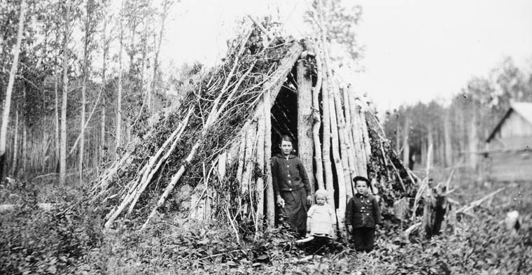 A woman and two children stand in the doorway of a lean-to in a wooded area.
