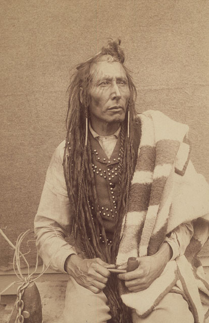 A man with long braids and a blanket over his shoulder holds a smoking pipe and looks pensive.