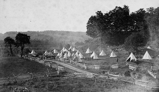 A dozen or so tents pitched in a field with a few trees surrounded by a simple wooden fence.