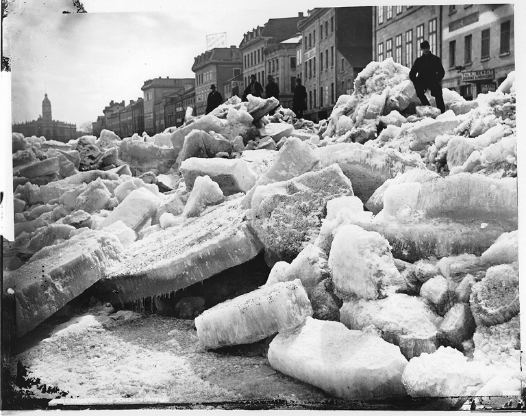 A man stands on top of a huge pile of ice.