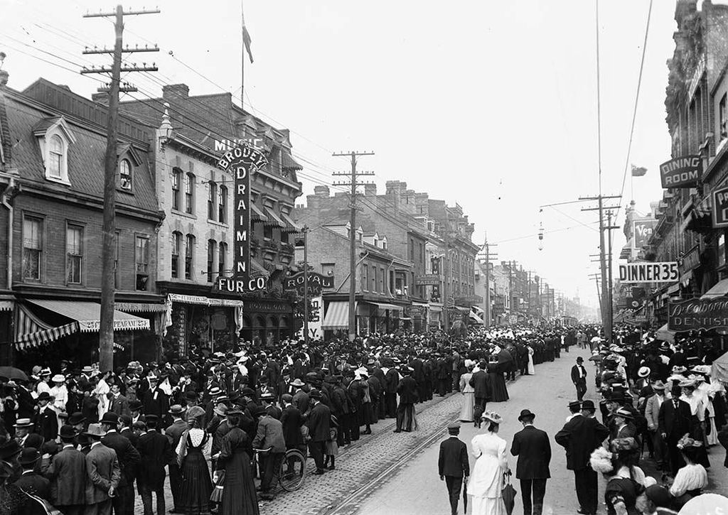 A city street packed with people at the turn of the century.