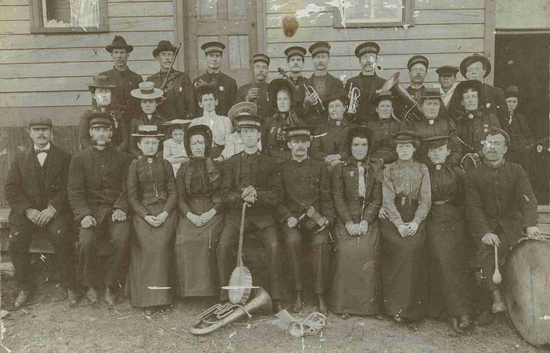 Three rows of men and women, some with musical instruments, pose in front of a wooden building.