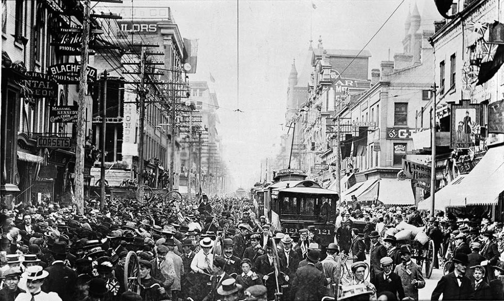 A packed city street with a street trolley surrounded by people.