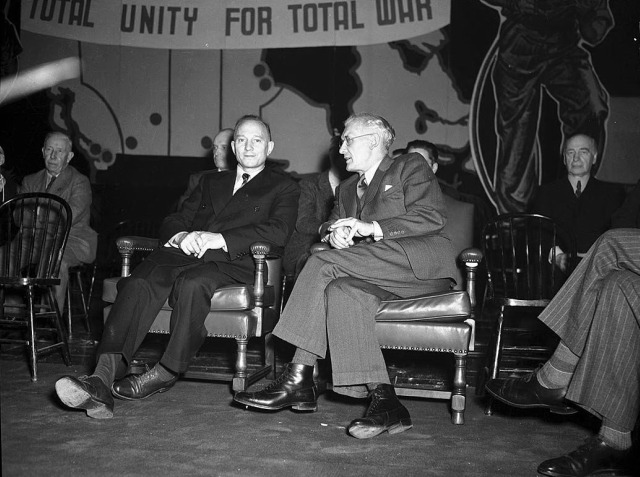 """Two men in suits sit in armchairs underneath a banner that says """"Total unity for total war."""""""