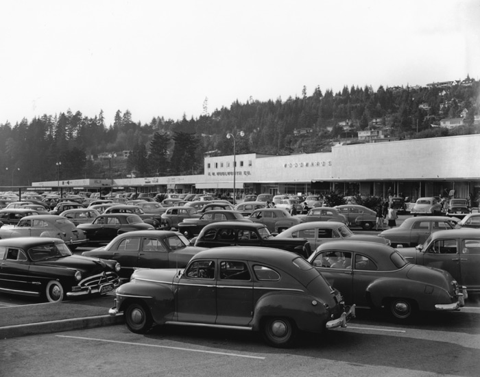 Cars crowd the parking lot of an early shopping mall.