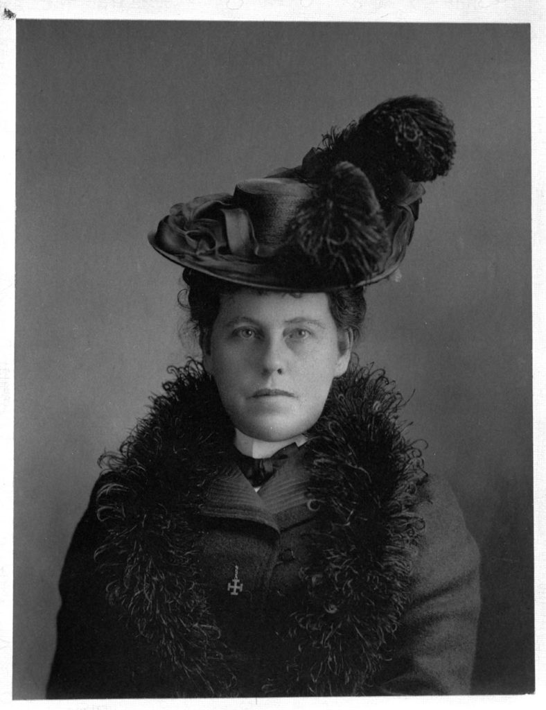 A woman wearing a feather boa and a hat with a feather looks at the camera.