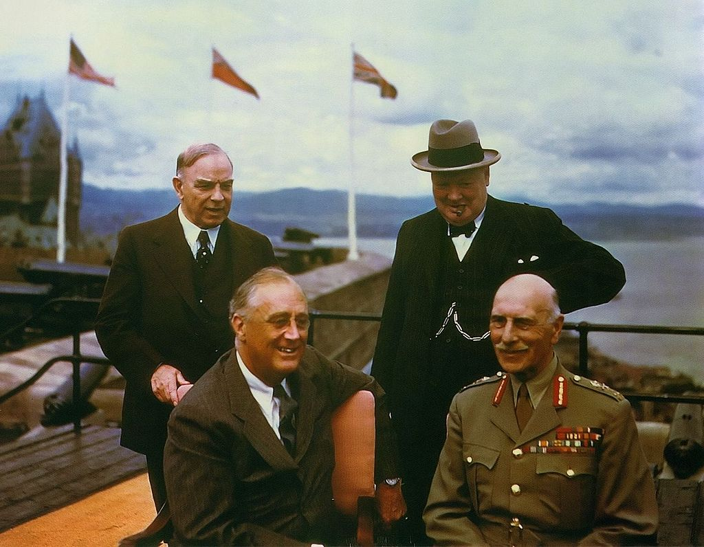 Four smiling middle-aged men pose together. Flagpoles and a body of water are in the background.