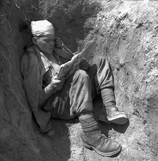 A soldier with a bandaged head sits in a foxhole, reading a comic book.