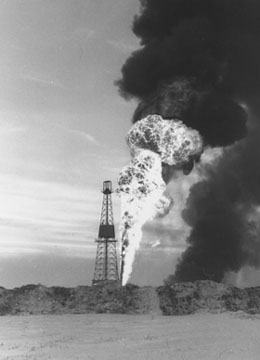 Behind an oil well, there is an explosion and a plume of black smoke.