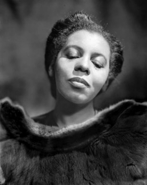 A black woman with a serene expression and an elegant fur wrap.