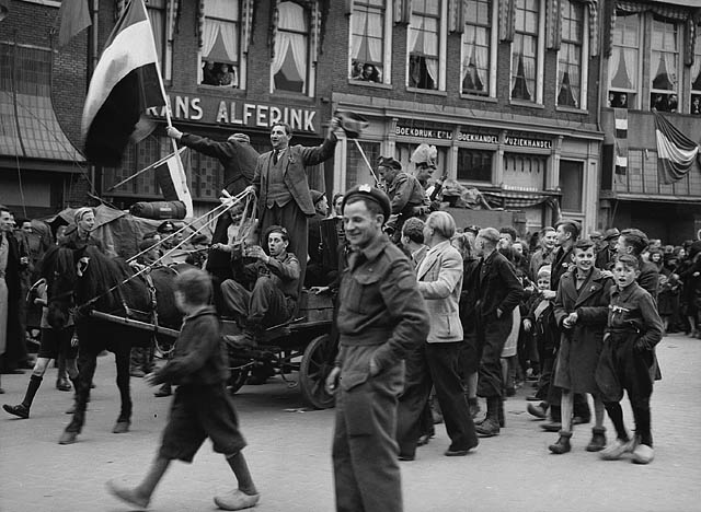 People celebrate in the street and hoist the Dutch flag. Children in wooden clogs walk by a soldier.