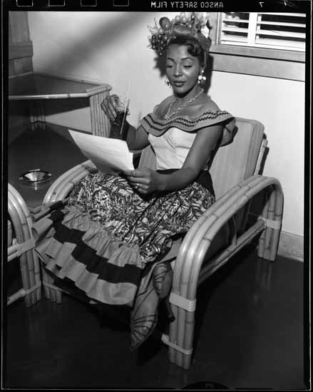 A young black woman reviews a document, drink in hand. She wears a Carmen Miranda–esque costume.
