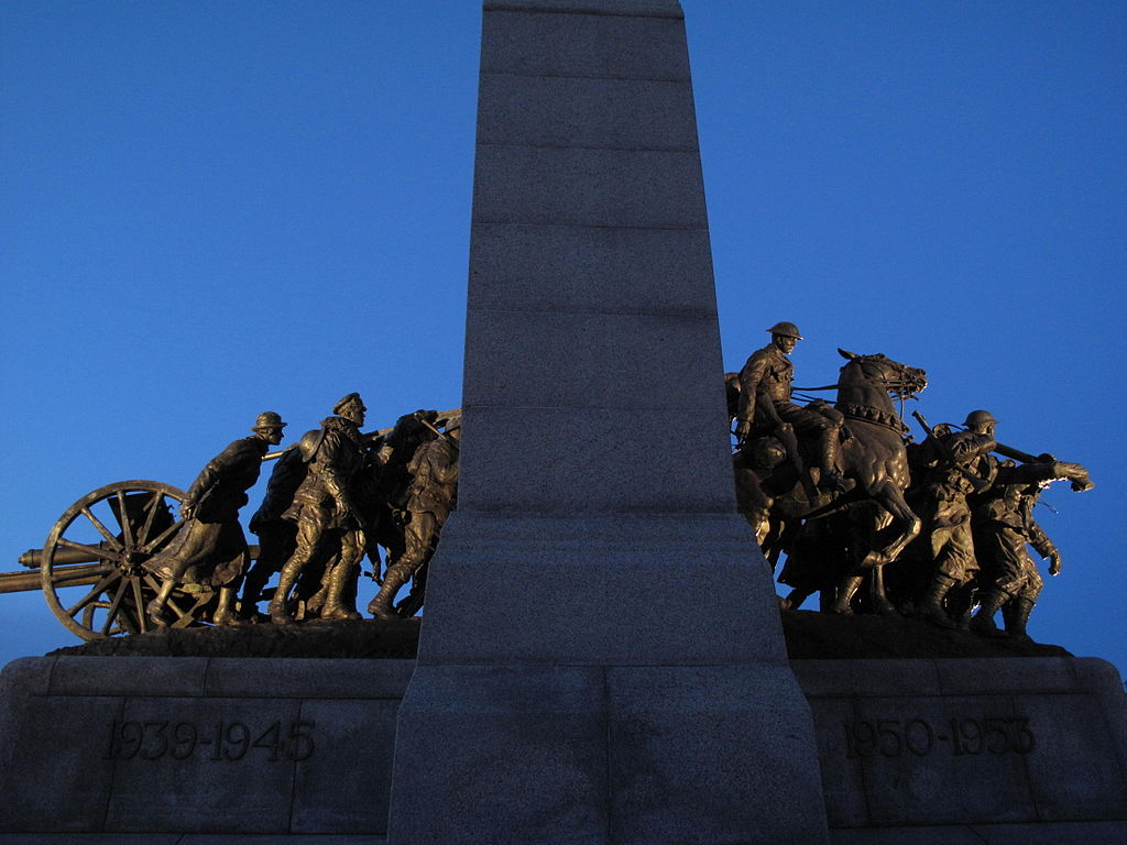 Bronze statue of weary soldiers. One rides a horse. The monument says 1939–1945 and 1950–1953.