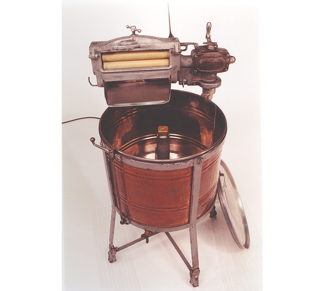 A clothes wringer is positioned above a copper basin.