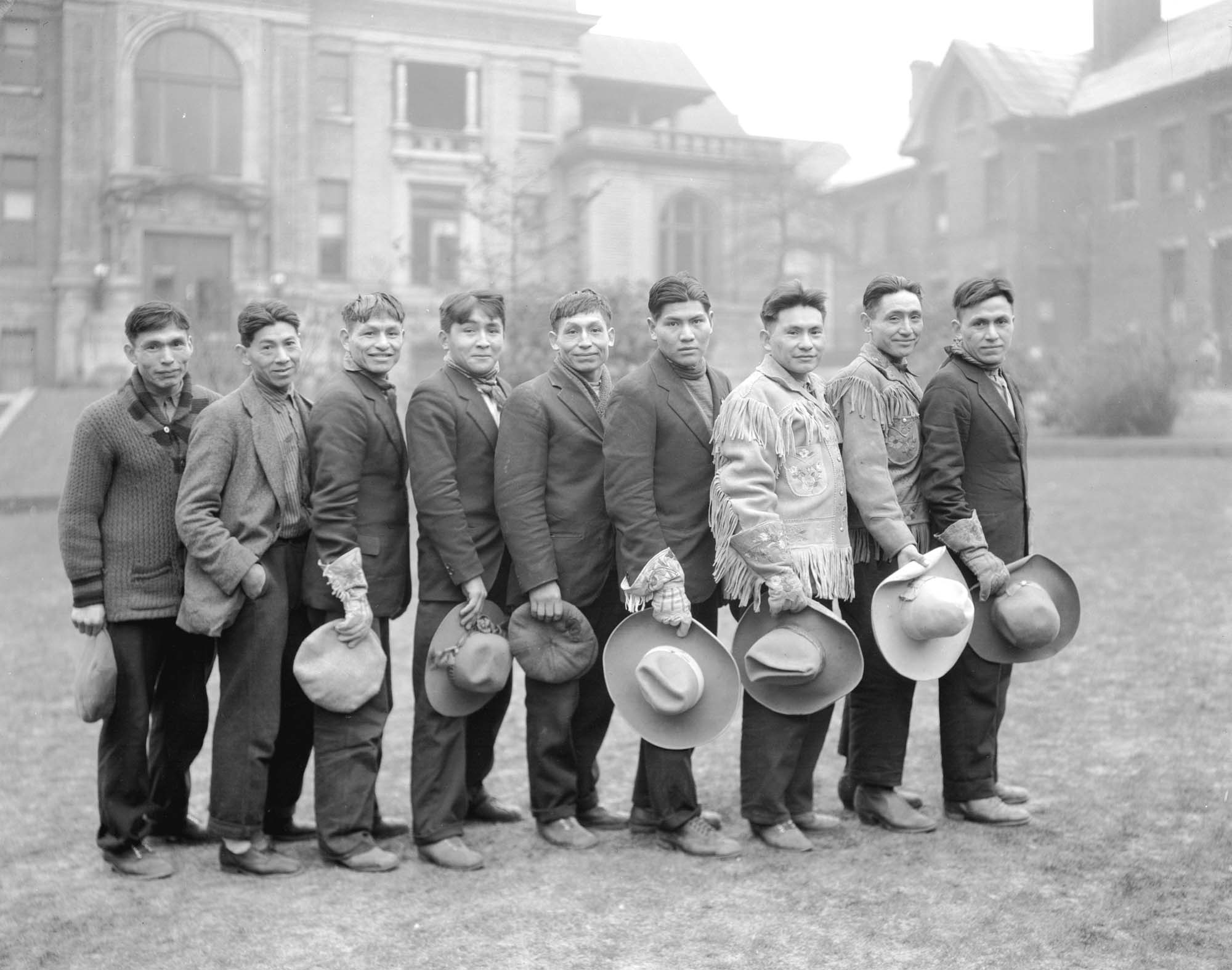 Nine men stand in a line, hats held in front of them, grinning.