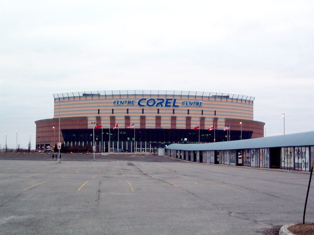 A hockey arena behind a parking lot.