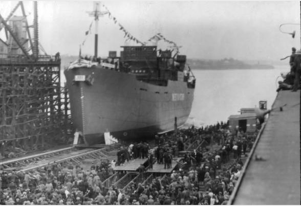 A large ship sits at a dock. Many people are gathered on the dock.