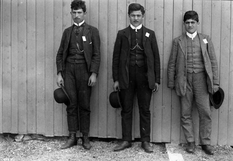 Three young men with white squares pinned to their suits stand in a line.