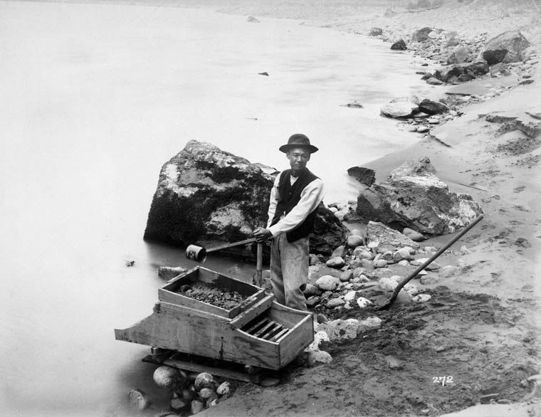 Man washing gold at riverside using a wooden box with a metal grate.