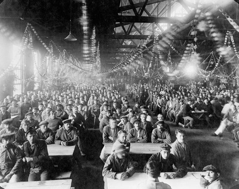 Men sit in a packed mess hall. Paper chains hang from the rafters.