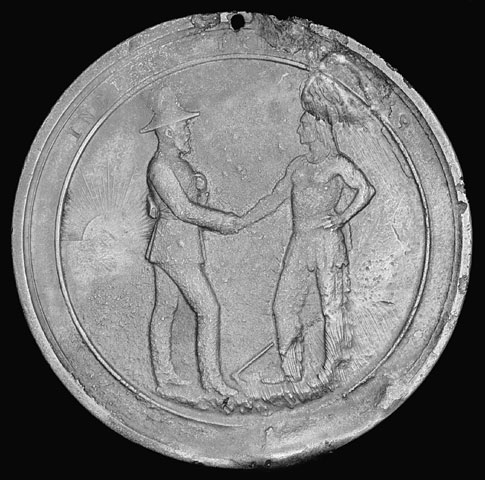 A medal showing a white man shaking hands with an Indigenous man wearing a headdress.