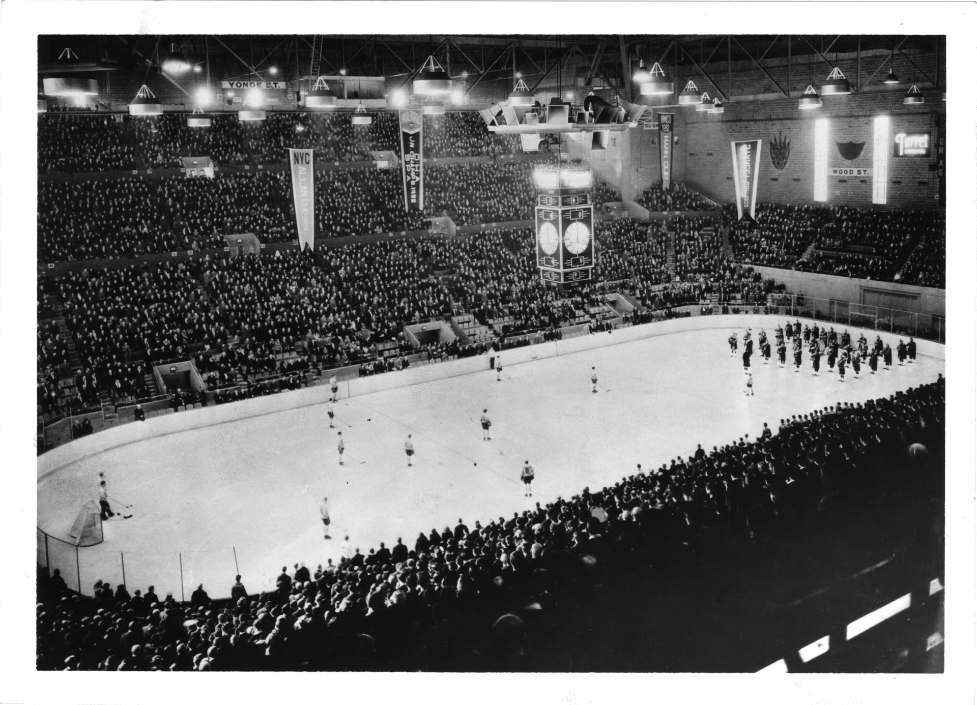 A packed hockey arena. One team and a marching band are on the ice.