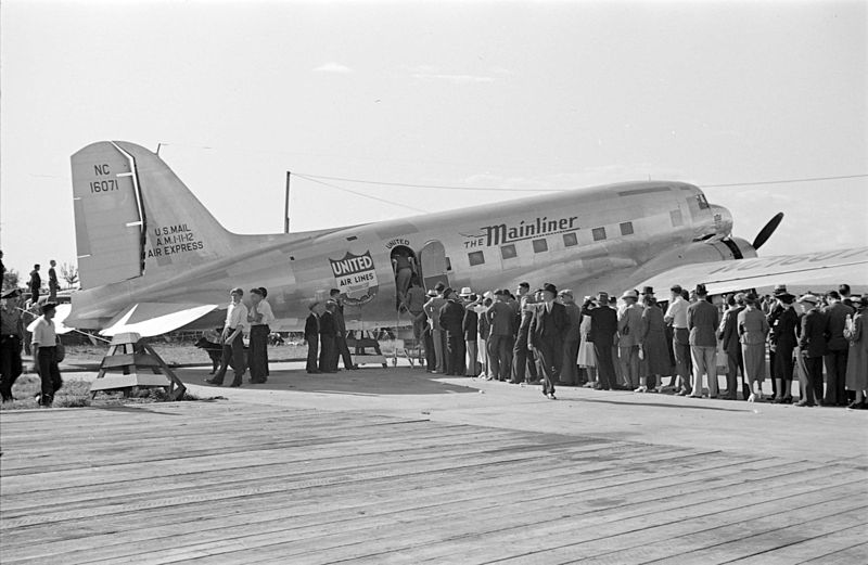 A line of passengers wait to board a small airplane.