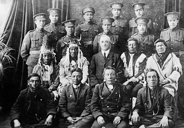 Two rows of Indigenous soldiers and two of elders, some of whom are in traditional regalia.