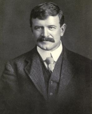 A photo portrait of a man in a suit with a thick moustache.