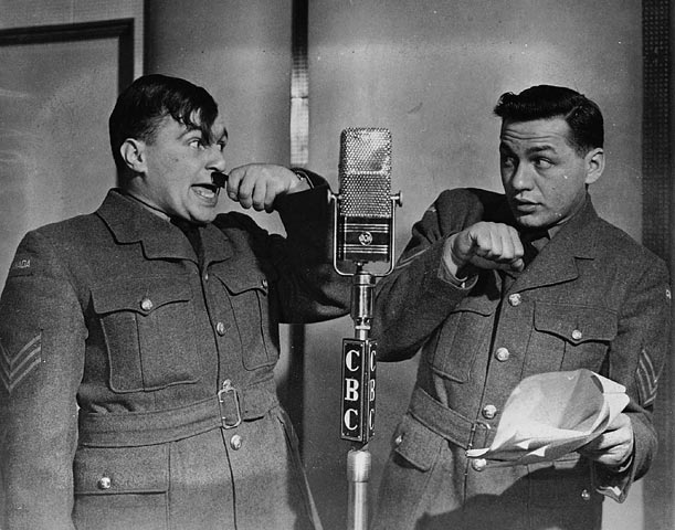 Two men in military uniforms stand by a broadcast microphone. One holds a small comb under his nose.