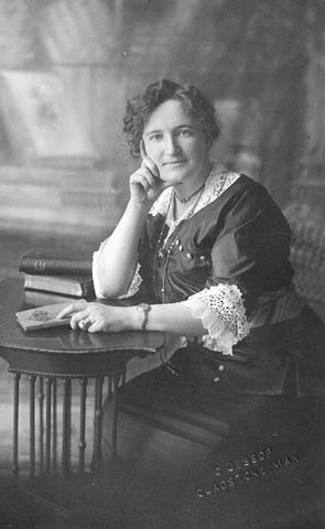 A woman with short curly hair sits at a small table with a few books.