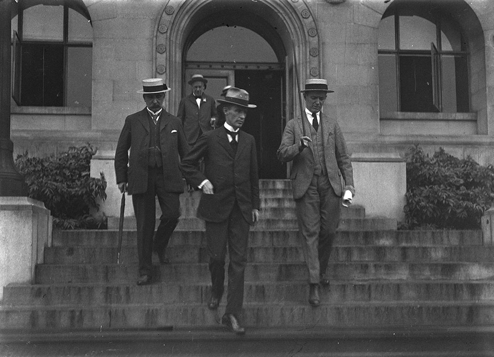 Four men in suits and flat straw boater hats descend stone steps.