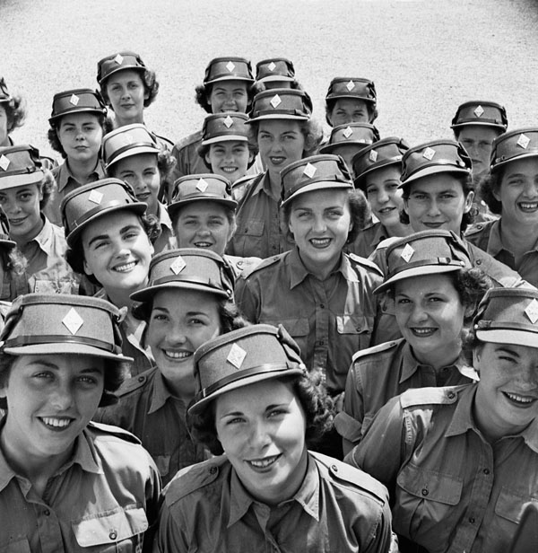 Two dozen women in military uniforms gather close and smile.