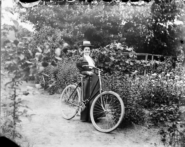 A woman in a Victorian dress poses with a bicycle in a garden.